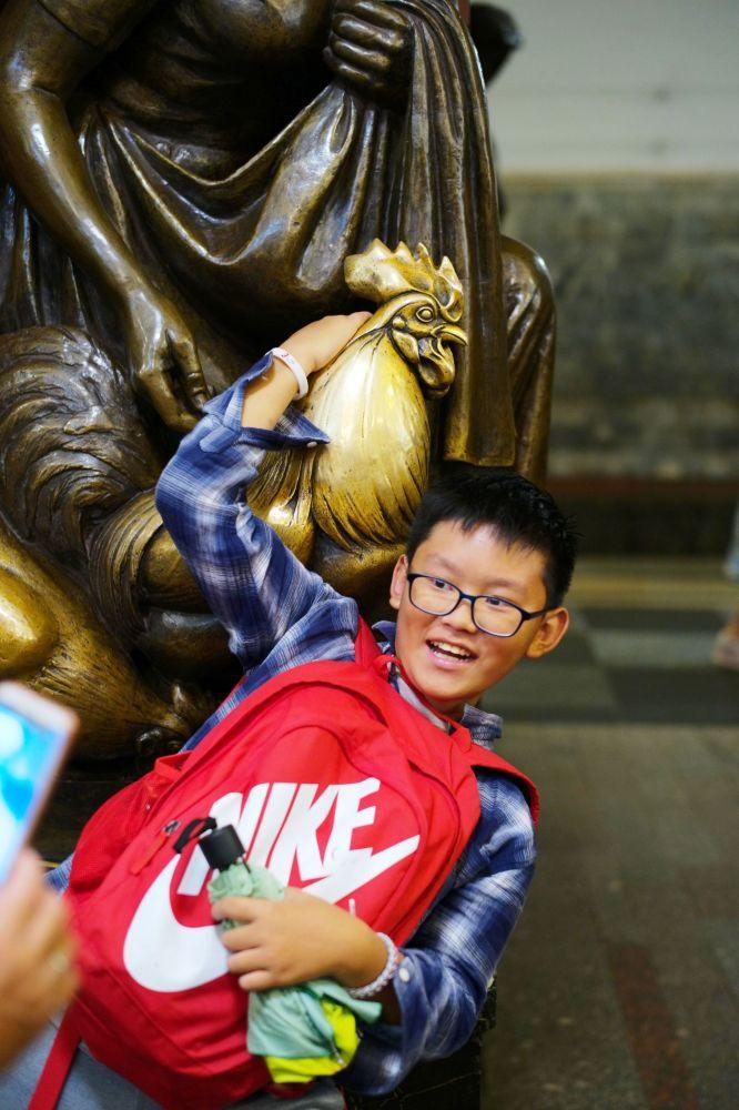 """Chłopiec fotografuje się przy rzeźbie na stacji  metro """"Plac Rewolucji"""""""