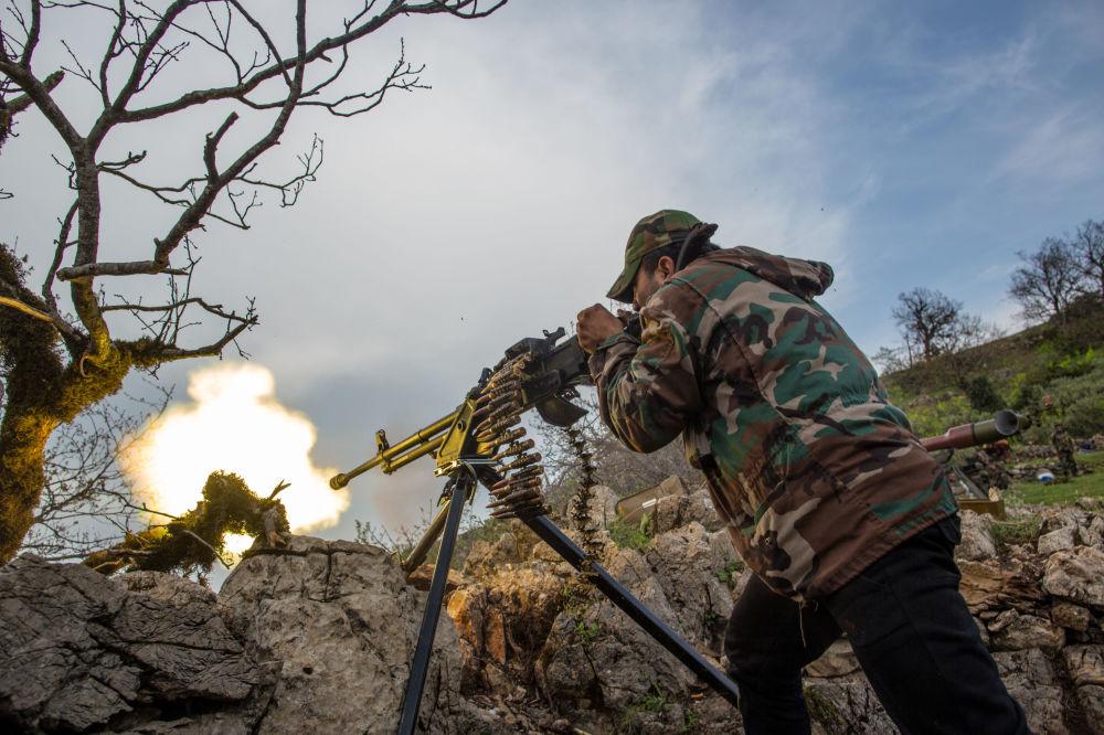 Żołnierz armii rządu syryjskiego strzela z karabinu maszynowego na jednym ze szczytów w pobliżu miasta Kessab