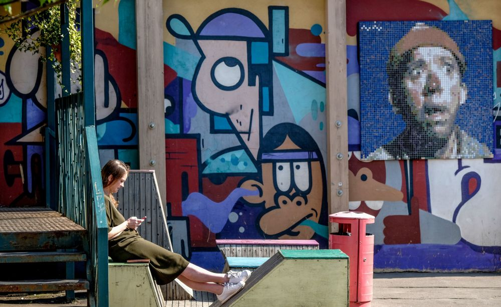 Dziewczyna odpoczywa na świeżym powietrzu przy bloku, którego ścianę zdobią graffiti przedstawiające Jurija Nikulina