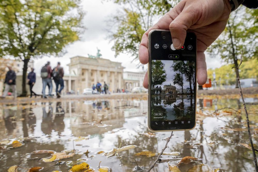 Mężczyzna fotografuje na telefon Bramę Brandenburską w Berlinie