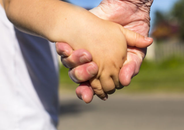 Dorosły prowadzi dziecko za rękę