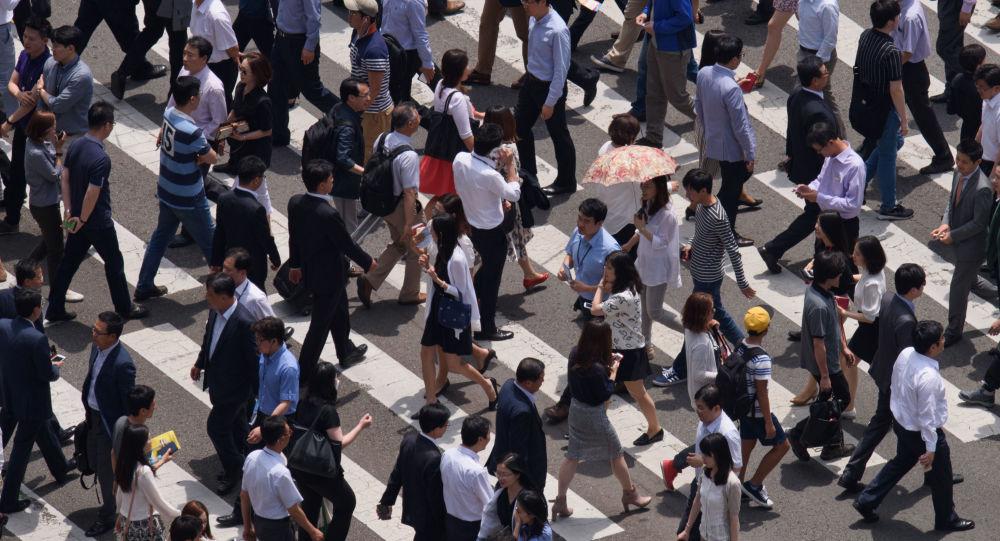 Ludzie przechodzą przez ulicę w Seulu