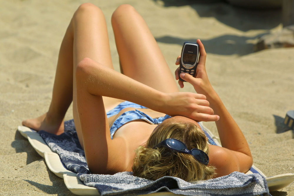 Dziewczyna na plaży z telefonem komórkowym Nokia, 2003 rok