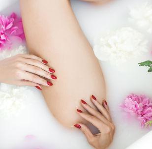 Kobieta w kąpieli z mleka i kwiatów