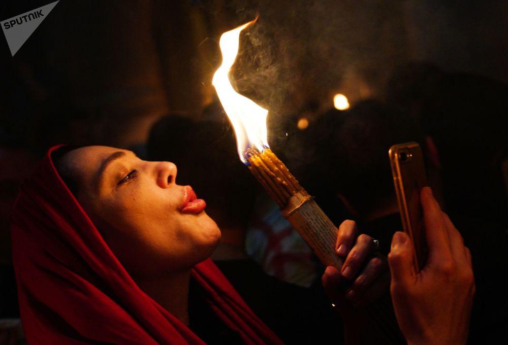 Kobieta świętuje zstąpienie Świętego Ognia w Świątyni Grobu Pańskiego.