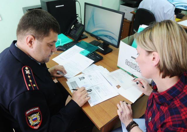 Funkcjonariusz policji i interesant w centrum wydawania rosyjskim paszportów mieszkańcom DRL i ŁRL w miejscowości Nowoszachtyńsk w obwodzie rostowskim