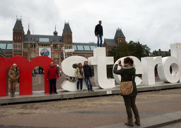 Turyści robią zdjęcia pod budynkiem Państwowego Muzeum Amsterdamu