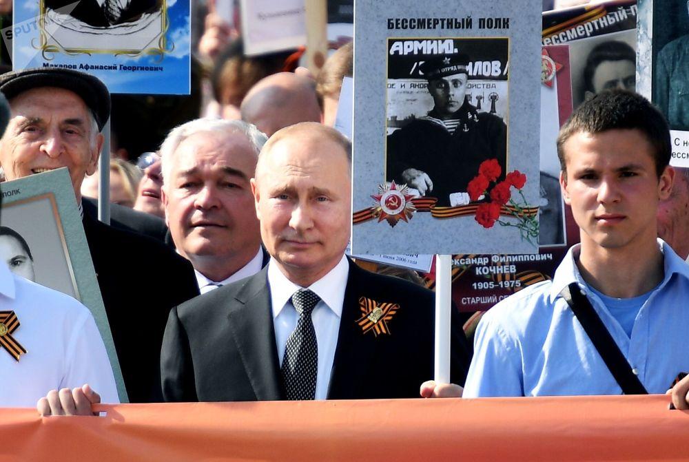 """Prezydent Rosji Władimir Putin z portretem swego ojca, żołnierza frontowego Władimira Spiridonowicza uczestniczy w patriotycznej akcji """"Nieśmiertelny pułk""""."""