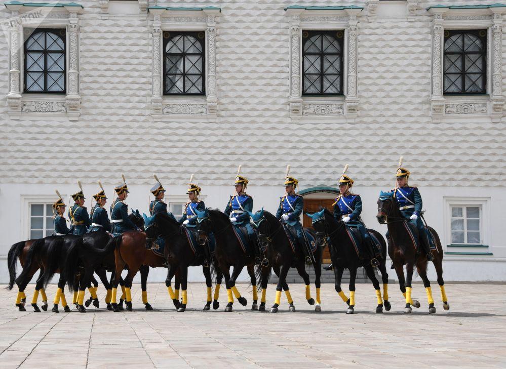 """Żołnierze Pułku Prezydenckiego podczas ceremonii rozejścia się pieszej i konnej straży z udziałem młodych jeźdźców """"Kremlowskiej Szkoły Jeździeckiej"""" na Placu Katedralnym Moskiewskiego Kremla."""
