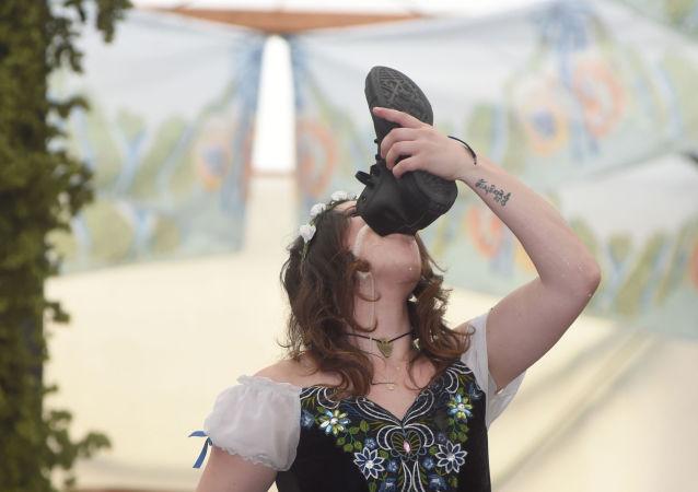 Kobieta pije piwo z butu podczas otwarcia festiwalu Oktoberfest w Monachium