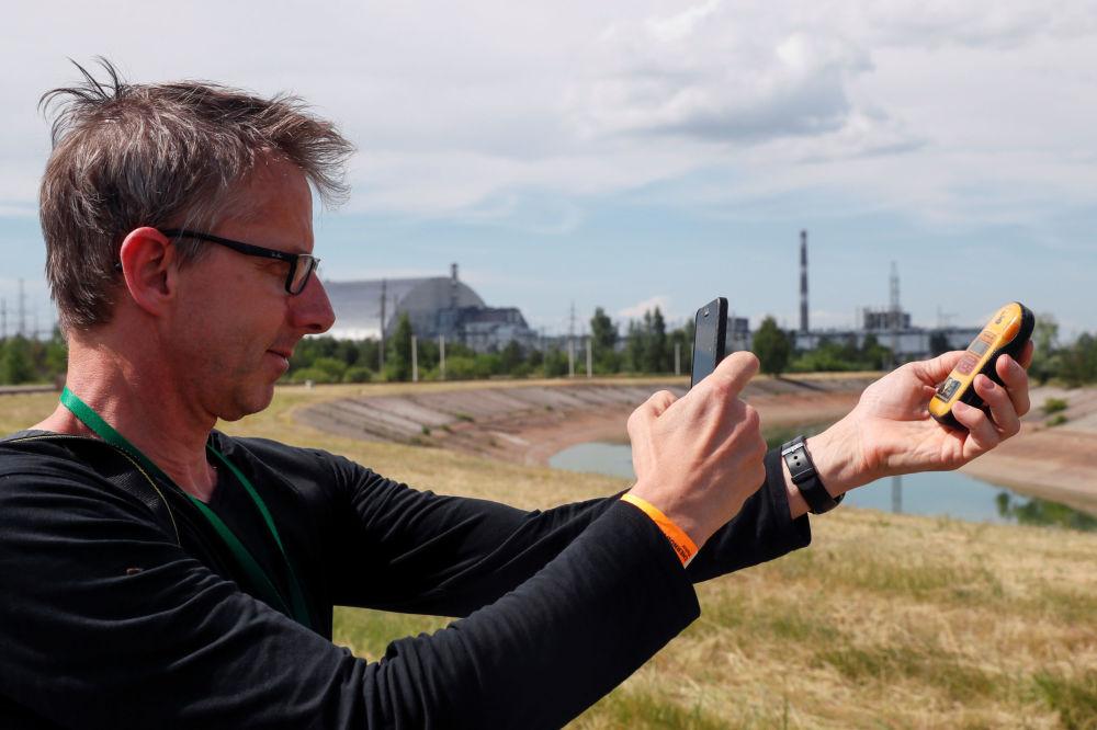 Mężczyzna fotografuje dozymetr w Czarnobylu