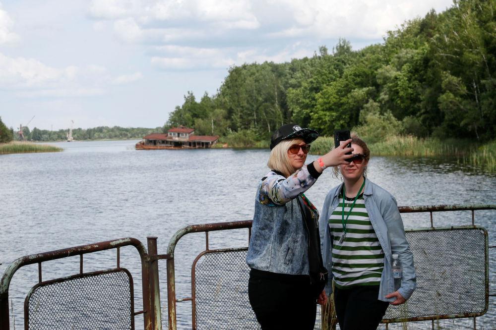 Turystki robią sobie selfie przy rzece w mieście Prypeć