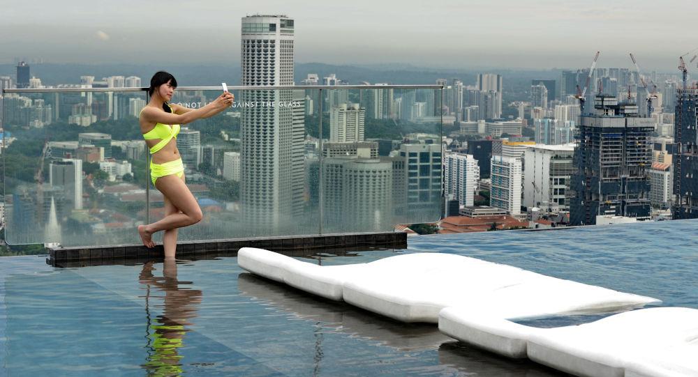 Kobieta robi sobie selfie na dachu hotelu Marina Bay Sands w Singapurze