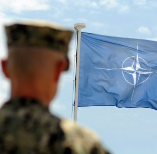 Żołnierz NATO na tle flagi NATO w Kosowie