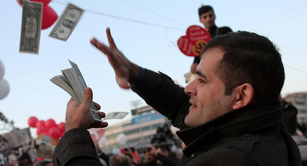 Mężczyzna rozrzuca imitację amerykańskich dolarów na znak protestu przeciwko korupcji w Turcji