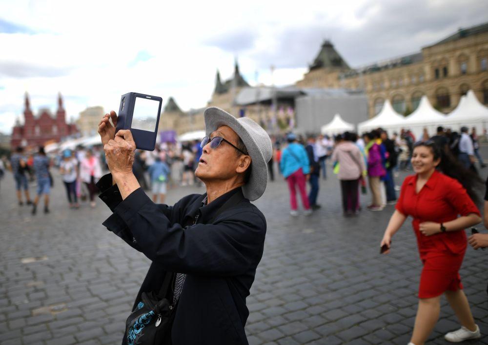 Chińscy turyści fotografują się na Placu Czerwonym w Moskwie