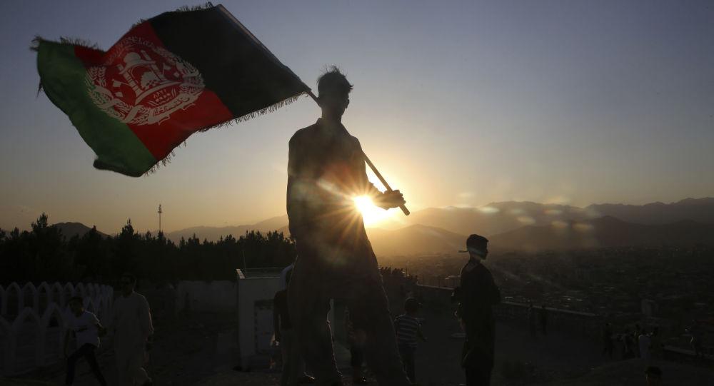 Mężczyzna z flagą Afganistanu