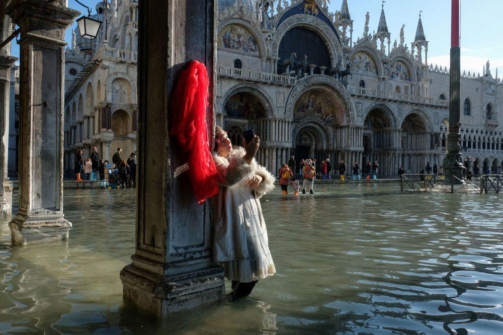 Turystka robi sobie zdjęcie podczas powodzi na Placu św. Marka w Wenecji