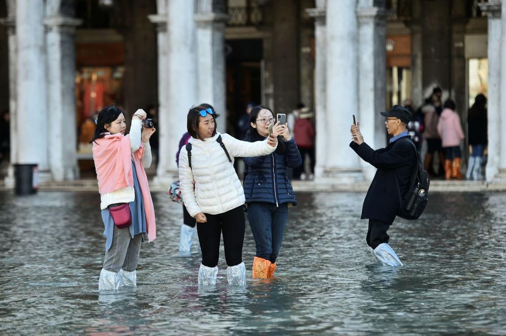Turyści podczas powodzi na Placu św. Marka w Wenecji