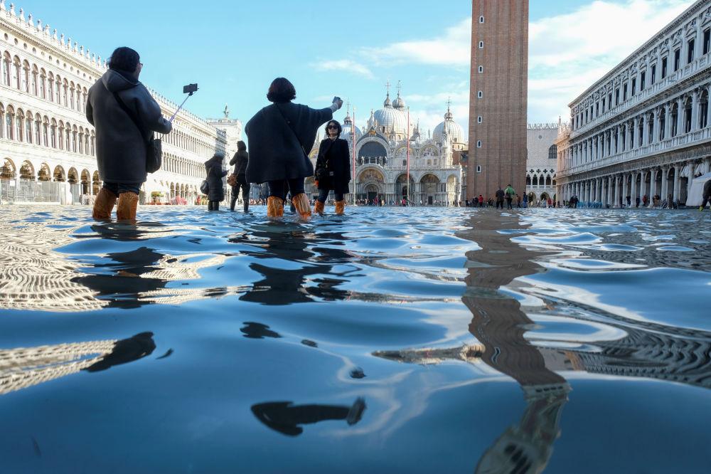 Turyści robią sobie zdjęcia podczas powodzi na Placu św. Marka w Wenecji