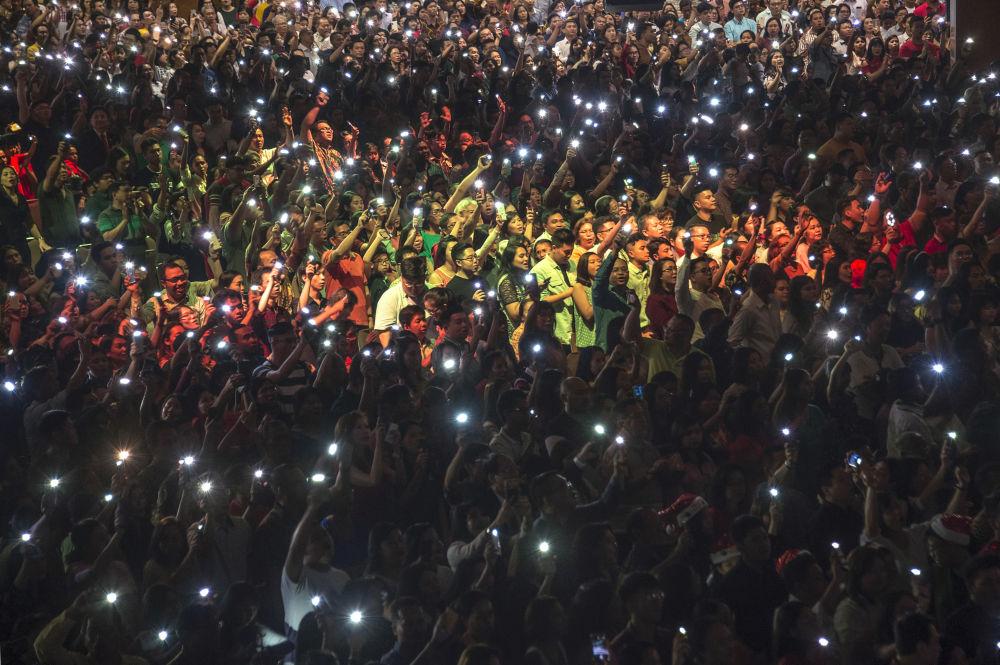 Chrześcijanie z zapalonymi latarkami na telefonach podczas mszy w Indonezji