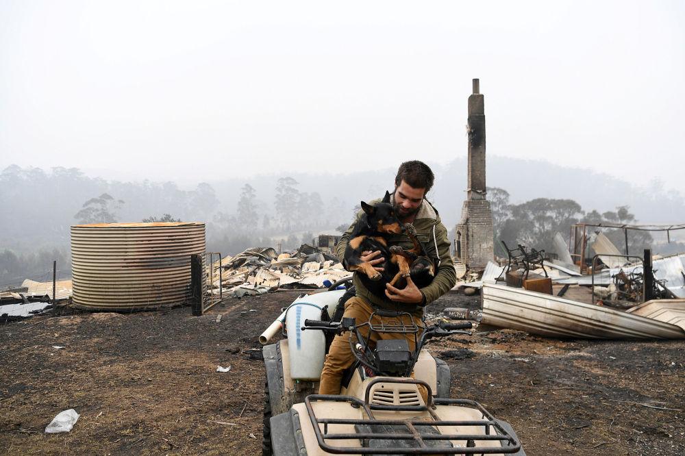 Mężczyzna z psem na tle swojej spalonej posiadłości