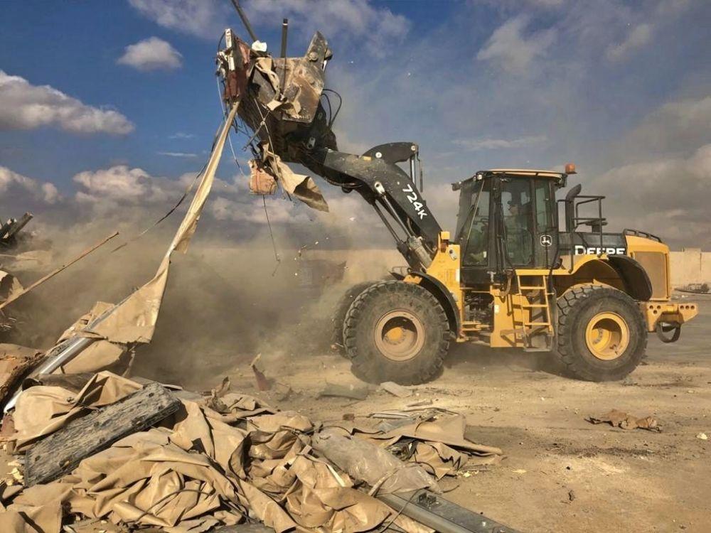 Spychacz usuwa gruz po ostrzelaniu amerykańskiej bazy wojskowej w Iraku