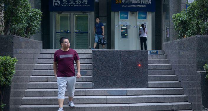 Ludzie obok bankomatu przy wejściu do banku w Pekinie
