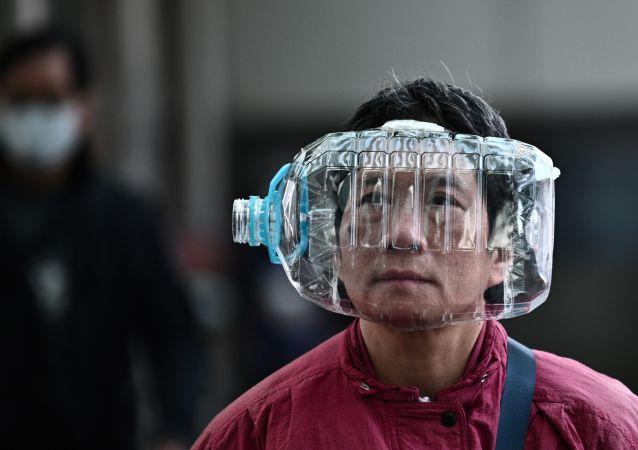 Mieszkaniec Hongkongu używa plastikowej butelki jako maski do ochrony przed koronawirusem