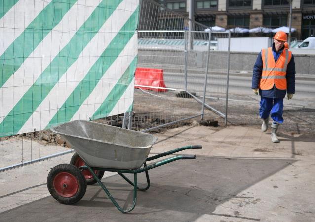 Pracownik budowlany z taczkami