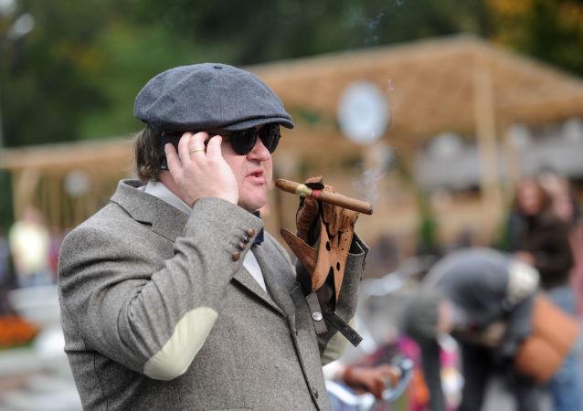 Uczestnik pali cygaro podczas festiwalu rowerowego w Moskwie w stylu angielskim