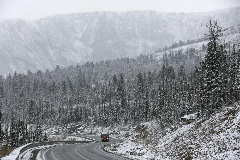 Ciężarówka jedzi o trasie Jenisiej M54 podczas opadu śniegu w Sajanach