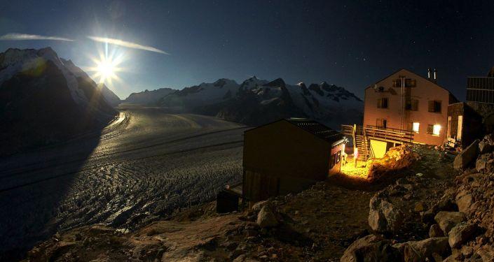 Księżyc nad lodowcem Aletschgletscher w Alpach