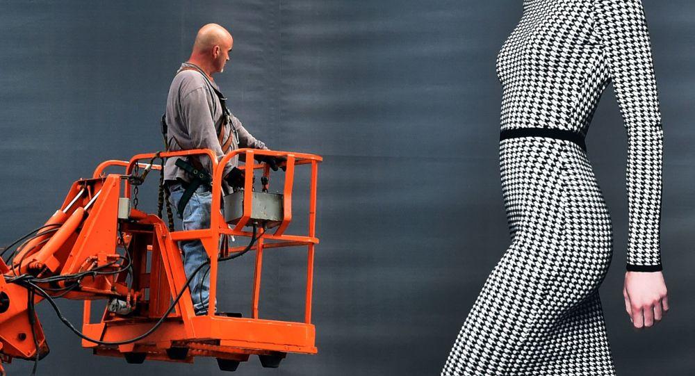 Разнорабочий рассматривает девушку на рекламном билборде Dressbarn в Нью-Йорке