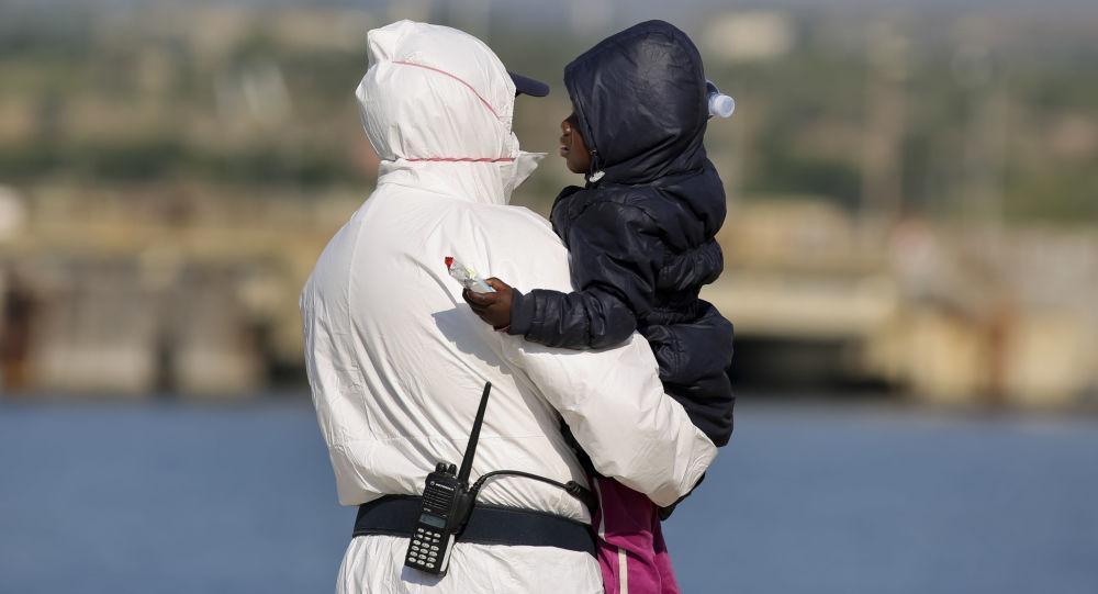 Oficer włoskiej straży przybrzeżnej niesie na rękach dziecko imigranta