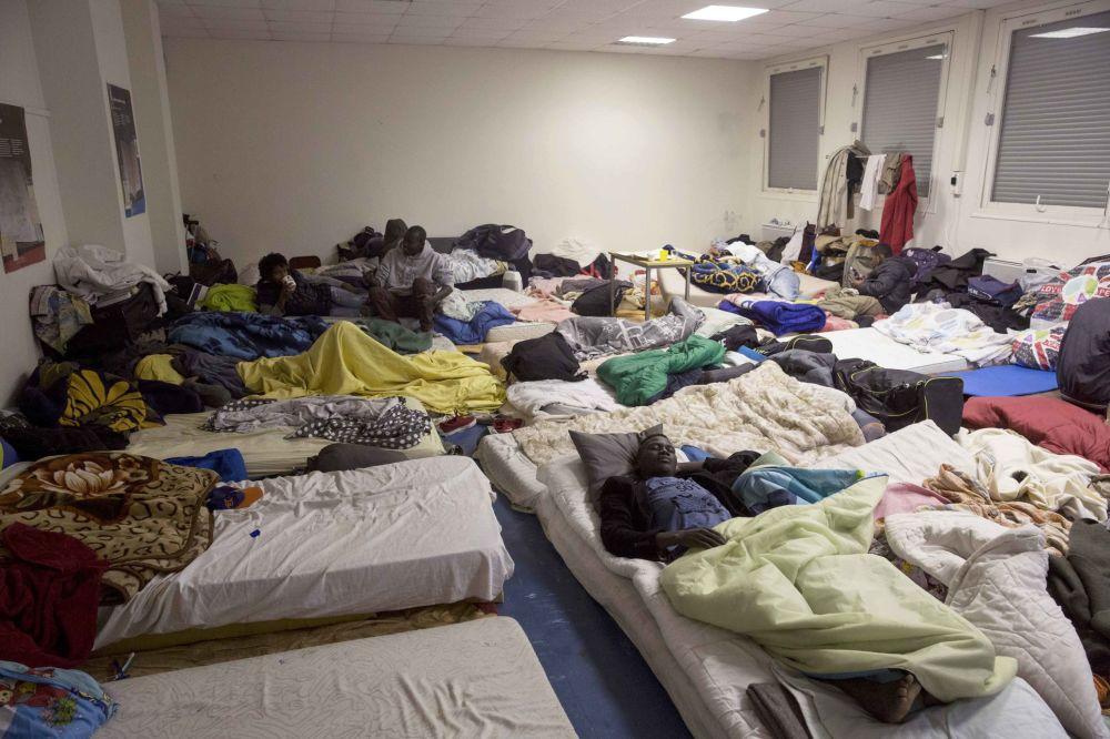 Migranci w budynku liceum imienia Jean Quarre w Paryżu