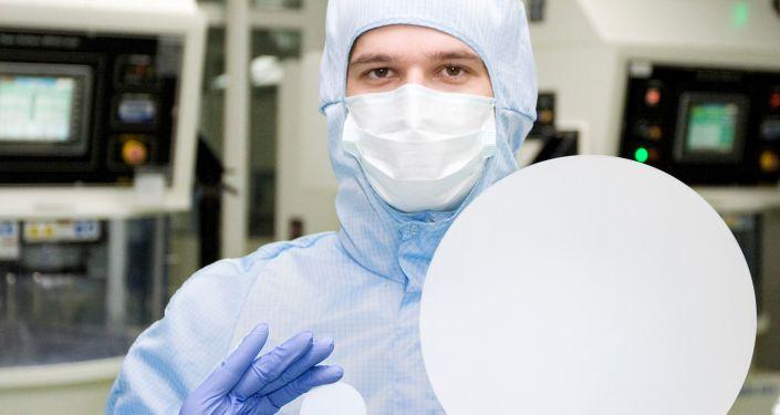 """Dziesięciocalowa i dwucalowa tafle syntetycznego szafiru prezentowane przez pracownika """"Monokryształu"""""""