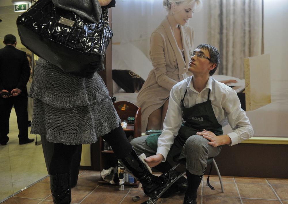 Mężczyzna czyszczący buty gościowi Pierwszego Międzynarodowego Festiwalu Kobiecego Femme Fest w Moskwie