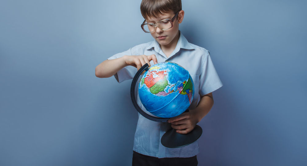 Chłopiec studiujący globus