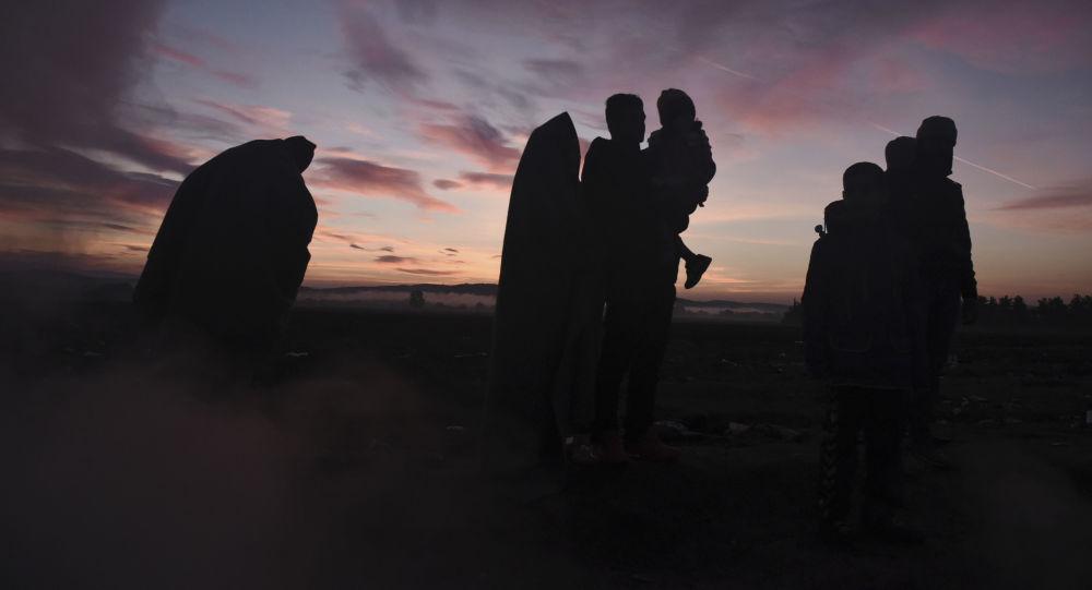 Sylwetki uchodźców z Bliskiego Wschodu na tle zachodu słońca