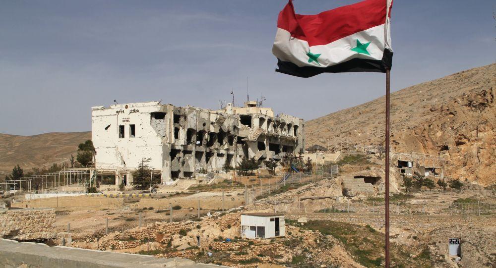 Syryjska flaga na tle zniszczonego domu w syryjskim mieście Maalula