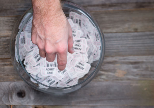 Ręka ciągnąca do pojemnika z losami