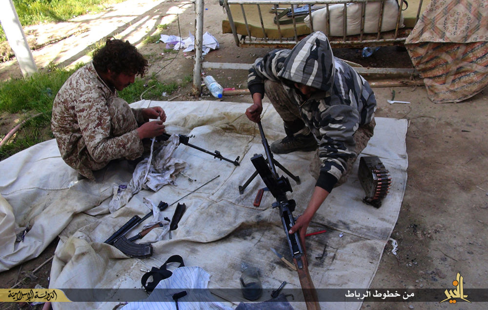Bojownicy Daesh czyszczą swoje karabiny w Syrii