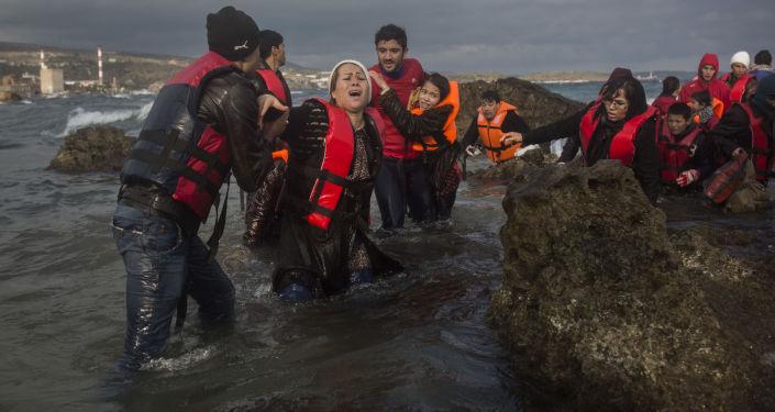 Bliskowschodni uchodźcy wysiadający z łodzi na wybrzeżu greckiej wyspy Lesbos