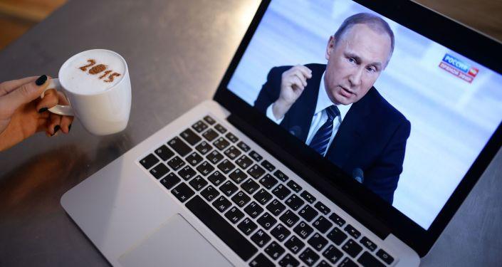 Mieszkanka nowosybirska ogląda reportaż jedenastej corocznej konferencji prasowej prezydenta Rosji Władimira Putina. 17 grudnia 2015