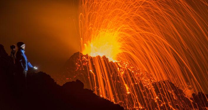 Mężczyzna patrzy na erupcję wulkanu Piton de la Fournaise na wyspie Reunion na oceanie Indyjskim