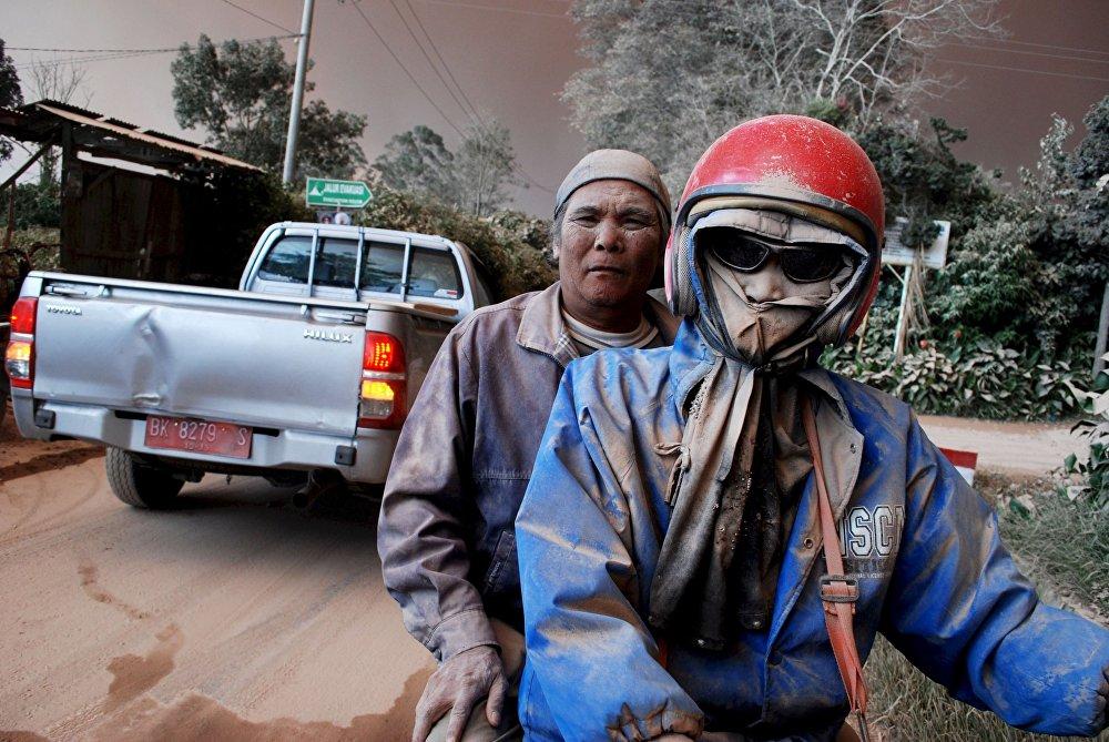 Ludzie, pokryci popiołem z wulkanu Sinabung