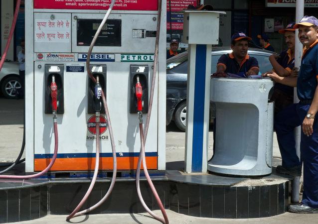 Pracownicy indyjskiej stacji benzynowej w oczekiwaniu na klientów