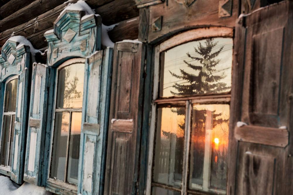 Słońce odbija się w oknach domu w miejscowości Tara dzielnicy Omskiej