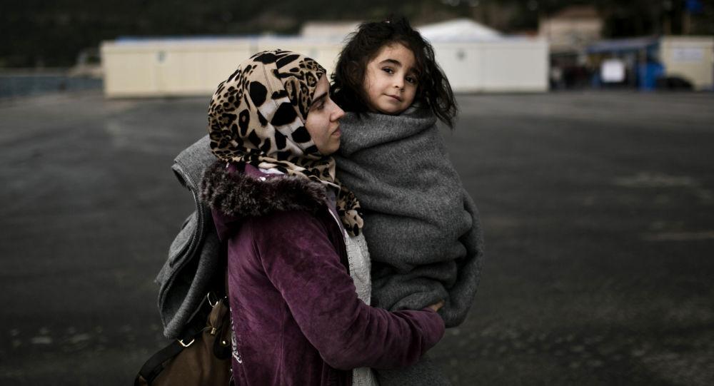 Kobieta trzyma dziecko na rękach w obozie dla uchodźców w Grecji